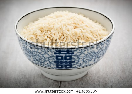 plain and uncooked rice in a chinese dishware. - stock photo