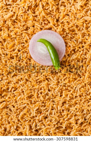 Plain biryani overhead view with garnish - Overhead view from the top of delicious plain biryani (kuska) made with basmati rice and various spices. Chilli, onion slice as garnish. Natural light used. - stock photo