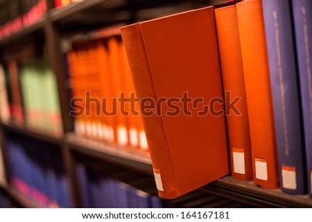 plain book jut out a bookshelf - stock photo