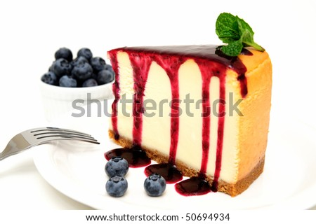 Plain Cheesecake with a Blueberry sauce poured over the top with fresh berries on the plate next to the cake and topped with a mint leaf. - stock photo