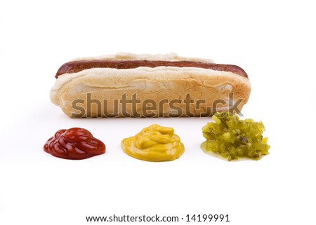Plain hotdog on a bun with ketchup, mustard, and relish in front.  Isolated on white. - stock photo