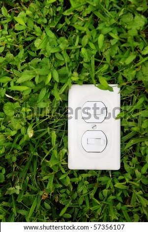 plain light switch over green grass - stock photo
