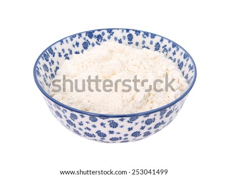 Plain or all purpose flour in a blue and white porcelain bowl with a floral design, isolated on a white background - stock photo