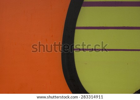 Plain orange and black, green, pink stripes on wall. - stock photo