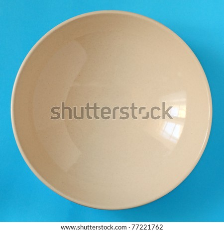 plain porcelain beige dish isolated in blue - stock photo