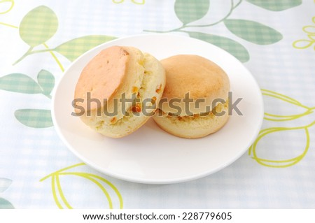 plain scone biscuit on a plate on tablecloth - stock photo