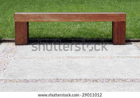 Plain Simple Wooden Bench On Footpath In A Park - stock photo
