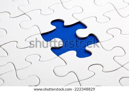 Plain white jigsaw puzzle, on Blue background, autism awerness symbol - stock photo
