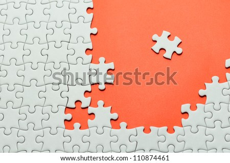 Plain white jigsaw puzzle, on orange background. - stock photo