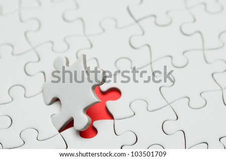 Plain white jigsaw puzzle, on Red background. - stock photo
