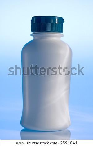 Plain white plastic pill bottle on blue - stock photo