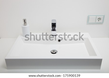 Plain white rectangular sink or handbasin in a modern bathroom with an electric wall socket above it - stock photo