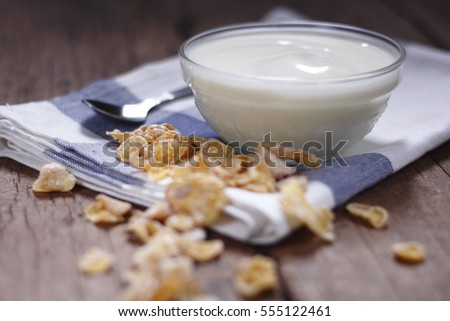 plain yogurt in small glass bowl with crispy cereal on cotton cloth place on old wood background. white yoghurt. plain yogurt. yoghurt.