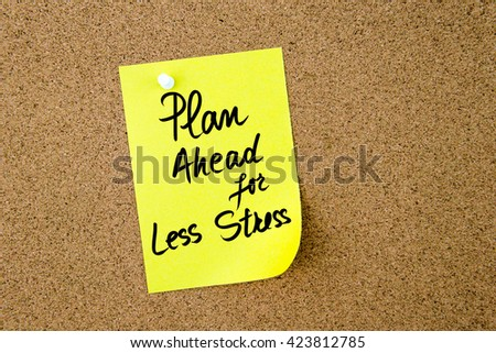 Plan Ahead For Less Stress written on yellow paper note pinned on cork board with white thumbtack, copy space available - stock photo