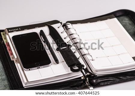 plan for murderer - calendar, planner, cellphone, pen and knife as weapon - stock photo