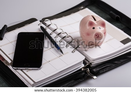 plan your future and business - calendar, planner, cellphone, pen and pig money box - stock photo