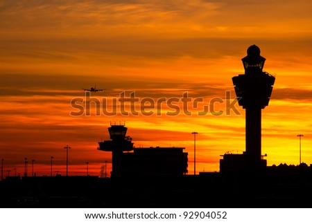 Plane arriving at Amsterdam-Schiphol airport during sunset - stock photo