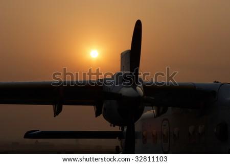 Plane at sunrise in Kathmandu airport, Nepal - stock photo