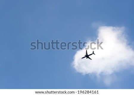 plane crossing a cloud  - stock photo