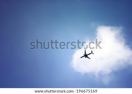 plane crossing a cloud vignette - stock photo