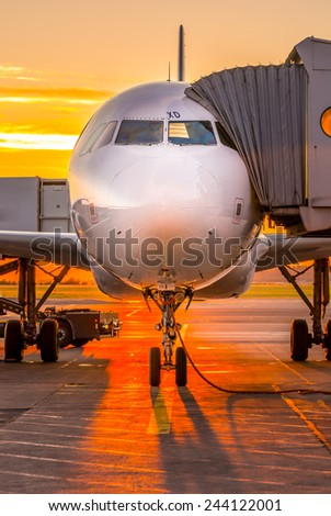 Plane docked at gate in sunset - stock photo