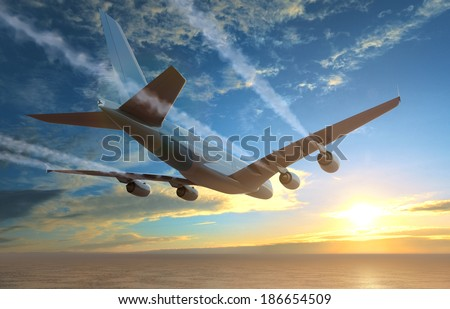 Plane flies over the sea at sunset - stock photo