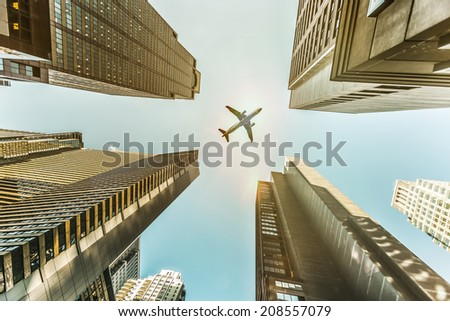 Plane flying above skyscrapers. - stock photo