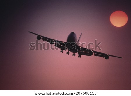 Plane Flying at Sunset