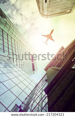 plane flying over highrise office buildings seen from below, Frankfurt am Main, Germany - stock photo