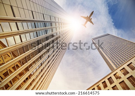 plane flying over office buildings in Frankfurt am Main, Germany - stock photo