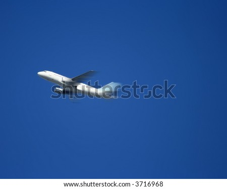 Plane flying overhead with a blue sky background.  Motion blur added for sense of movement and speed. - stock photo