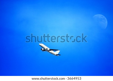 Plane flying overhead with the moon and a bluish sky in the background. - stock photo