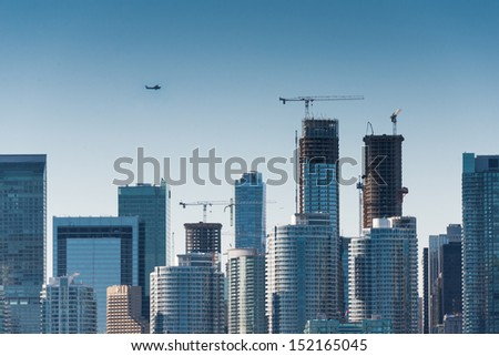 Plane flys over the city (Building signs are removed) - stock photo