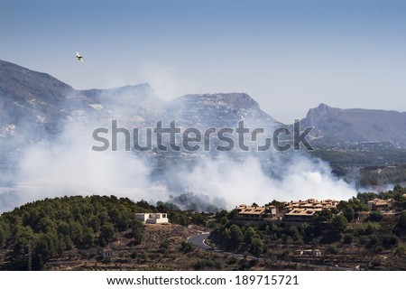 Plane in a fire burning mountain forest and village, danger for the houses - stock photo