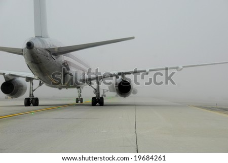 Plane in line for takeoff during fog - stock photo