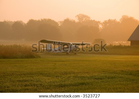 Plane in morning mist - stock photo