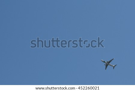 Plane in the clear blue sky, centered bottom right with copyspace