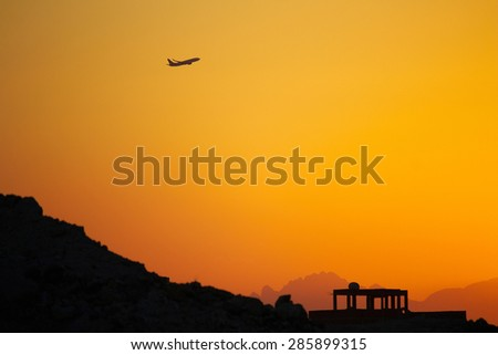 Plane in the sunset over the mountains - stock photo