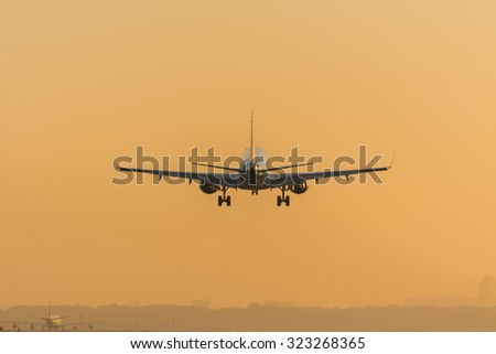 Plane is almost landed at the airport. Landed aircraft at the background. - stock photo