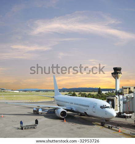 plane is boarding at airport and control tower is behind - stock photo