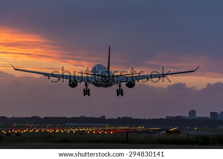 Plane is flying above the runway. Shot taken couple minutes before a nice cloudy sunrise. - stock photo