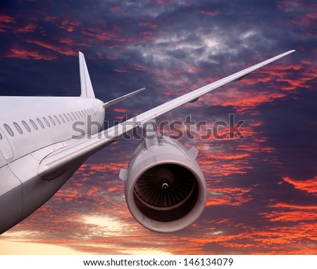 plane is flying at sunset. airplane on a background of the dawn sky landing or falling. - stock photo