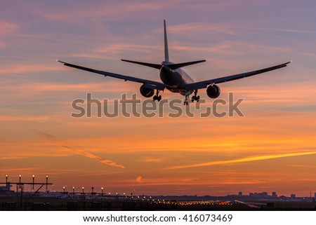 Plane is flying to the runway during a nice sunrise. - stock photo