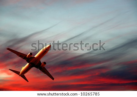Plane is flying while the sun is setting - stock photo