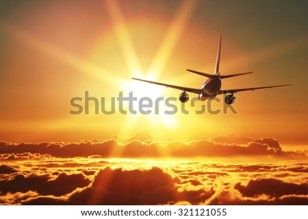 Plane is taking off at sunset - stock photo