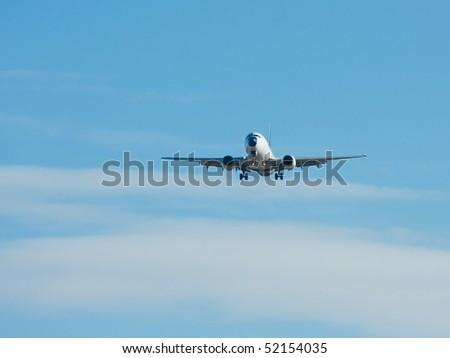 Plane landing against blue sky - stock photo