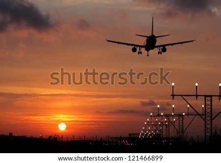Plane landing in a sunset. Back light - stock photo