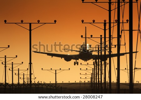 Plane landing in airport at sunset
