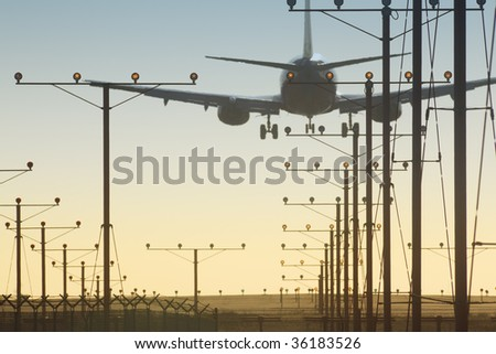 Plane landing  over runway in airport at sunset