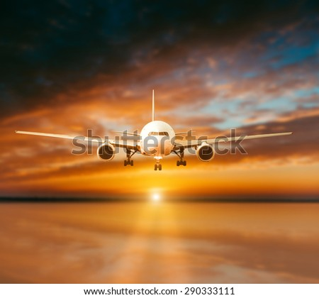 plane lands on the runway on a background of gorgeous sunsets - stock photo